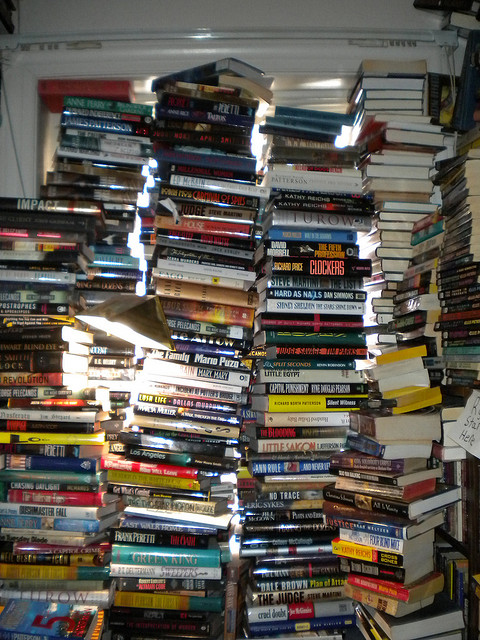 """Precarious Pile of Books"" by Lauren Orsini on flikr is licensed under CC by NC."
