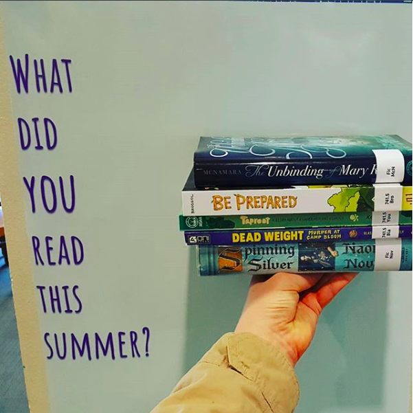 "Picture of a hand holding up books in front of a sign reading ""What did you read this summer?"""