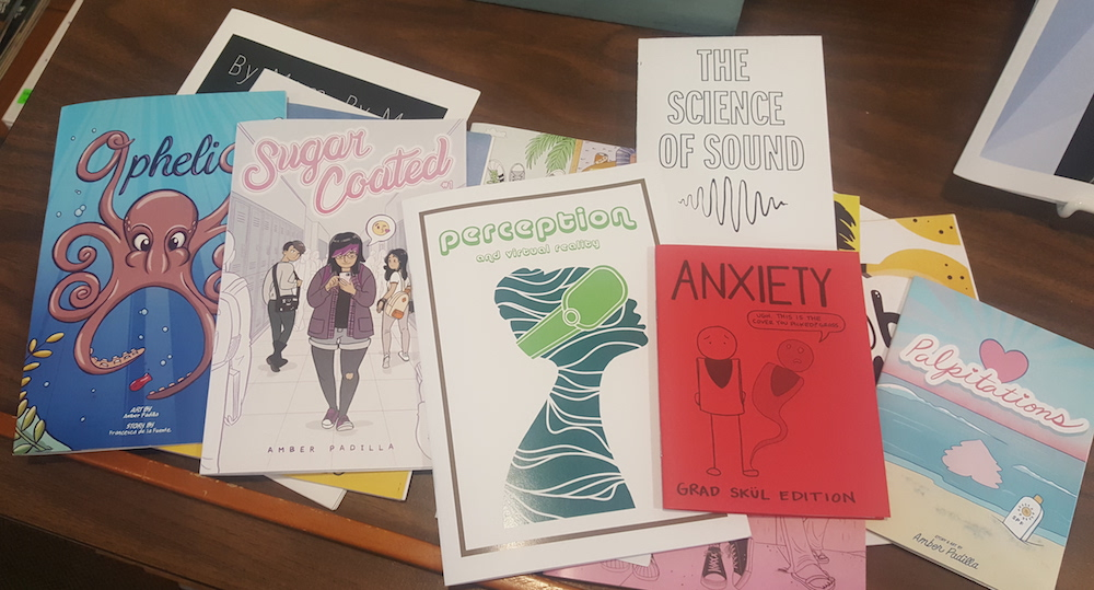 a photograph of several zines on a dark brown table