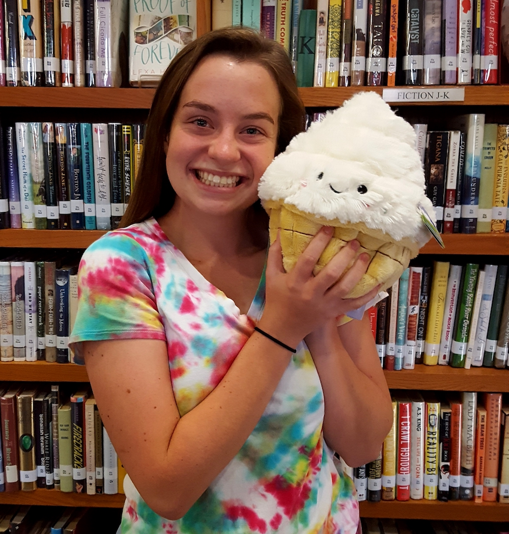 Smiling girl holding a stuffed cupcake.