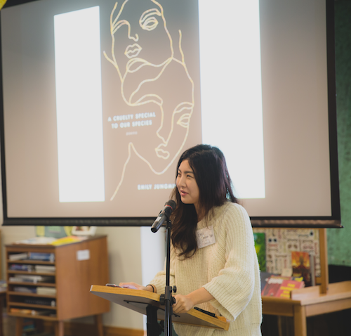 "Picture shows poet Emily Jungmin Yoon, a young Korean woman wearing a white sweater, standing at a podium. She is speaking into a microphone, and behind her is a projected image of her book ""A Cruelty Special to Our Species."""